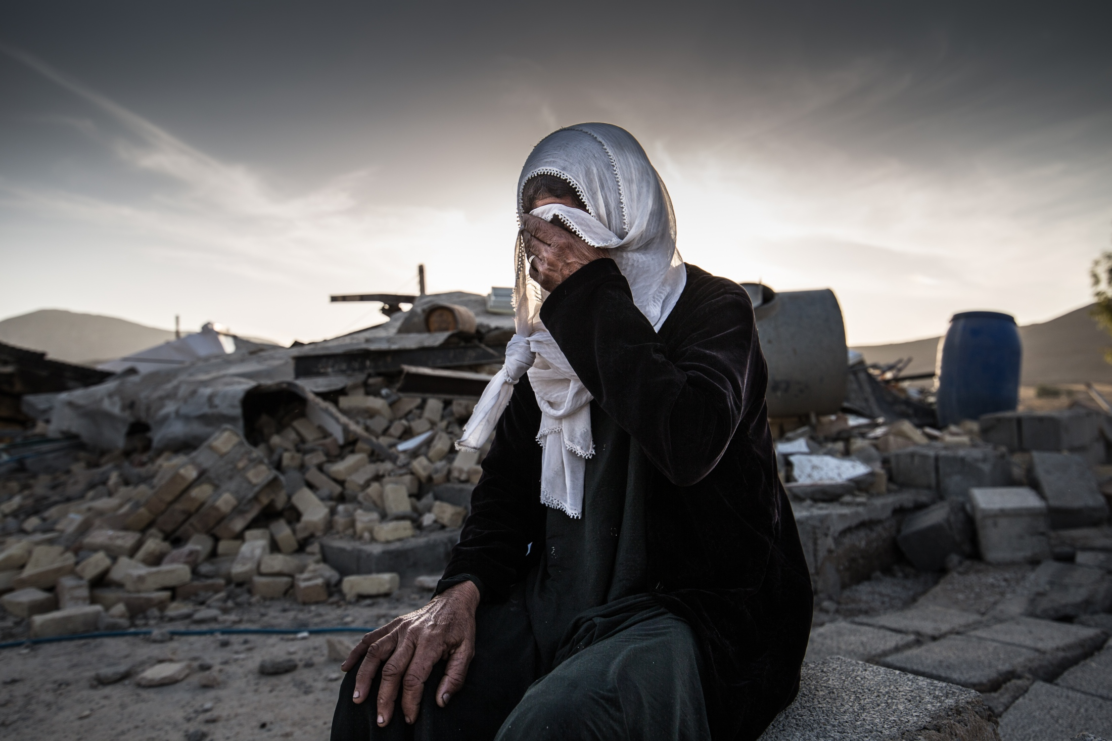 Keshvar, a 67-year-old woman from the village of Imam Ali Olya from Dasht-e Zahab of Kermanshah is crying on the ruins of her home.
