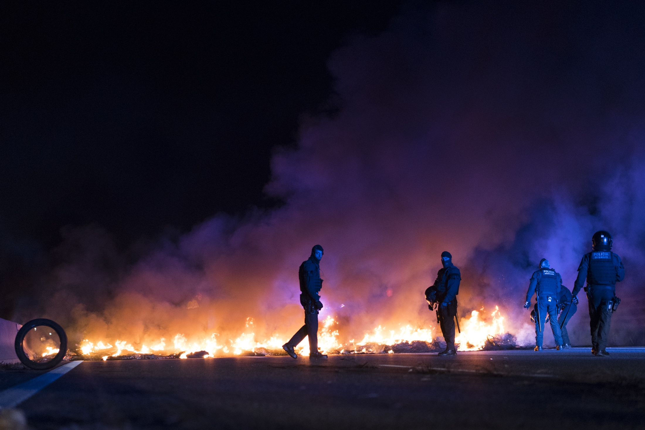 (AP Photo/Daniel Cole) Police officers try to remove burning tires blocking a highway, set by demonstrators protesting the imprisonment of pro-independence political leaders, during a general strike in Catalonia, Spain, Thursday, Feb. 21, 2019.