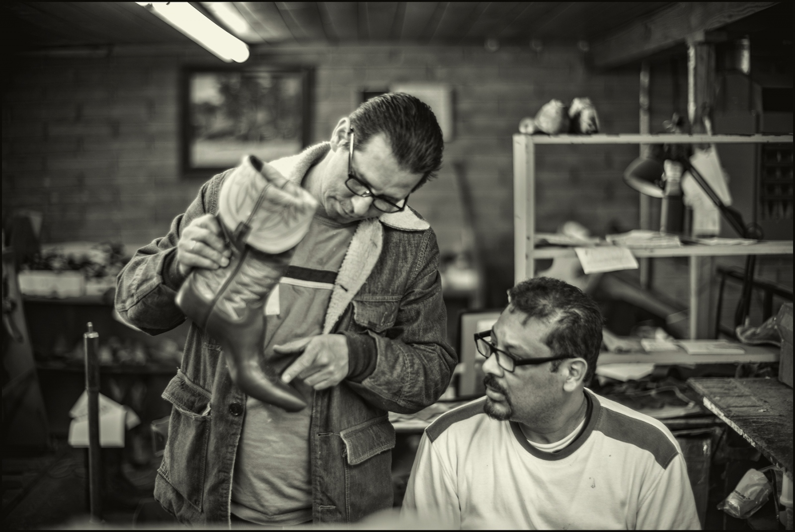 Juan eight years into his boot making career gives advice to Giovanni a second year boot artisan . Paul Bond Boot Company, Nogales, Arizona. February 2019.