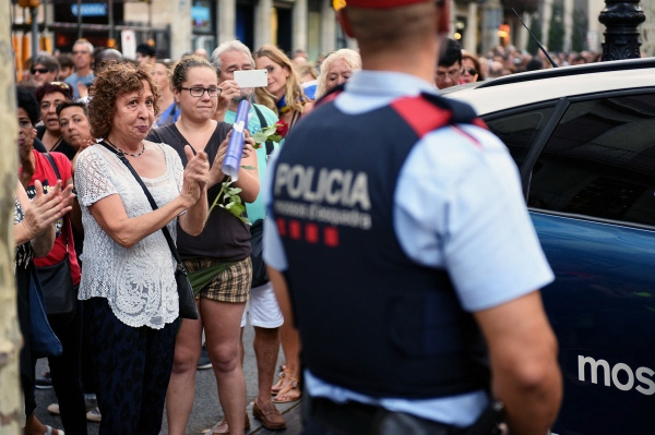 A woman is moved in front of Mossos d'Esquadra, the Catalan national police, on the day of the protest for the terrorist attack in Barcelona on 17 August. A van drove several people on the Rambla street, the tourist center of the city. The Mossos d'Esquadra were congratulated by the civilian population for the work they performed on the day of the attack. Barcelona, Spain. Photo by Gemma Miralda. 26/08/2017