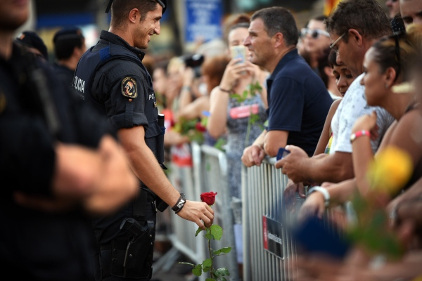 A mosso d'esquadra, nacional Catalan police,  holds a flower that has been given to him by a citizen, in gratitude for his work, the day of the attack in Barcelona, on 17 August. Barcelona, Spain. Photo by Gemma Miralda. 26/08/2017