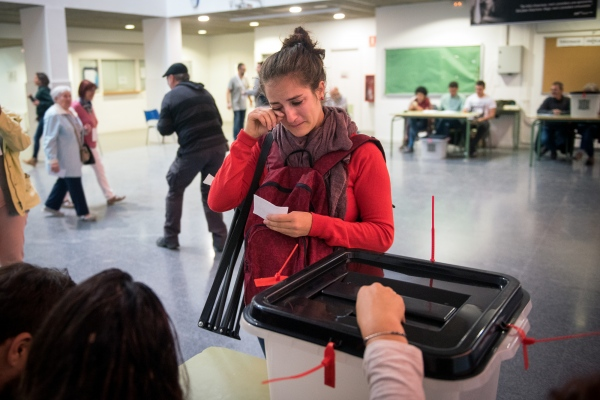 A woman is moved when she places her vote in the ballot box in the Referendum for the Independence of Catalonia. After a long wait for problems with the internet connection, she is the first to vote in this electoral college early morning. Terrassa, Spain. Photo Gemma Miralda 01/10/2017