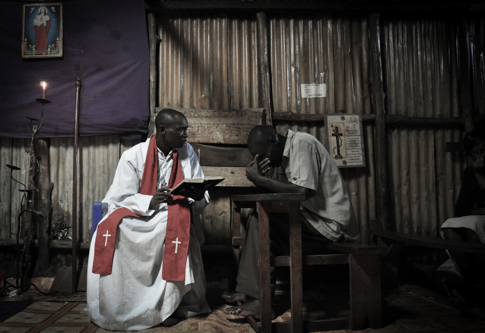Photography image -  A priest in the Nairobi slum of Kibera listens to a man who believes he has been possessed by a demon and has come to church to try and have it removed. While most priests in Kibera preach on Sundays, many turn to more unconventional healing methods during weekdays in order to earn a little extra income.