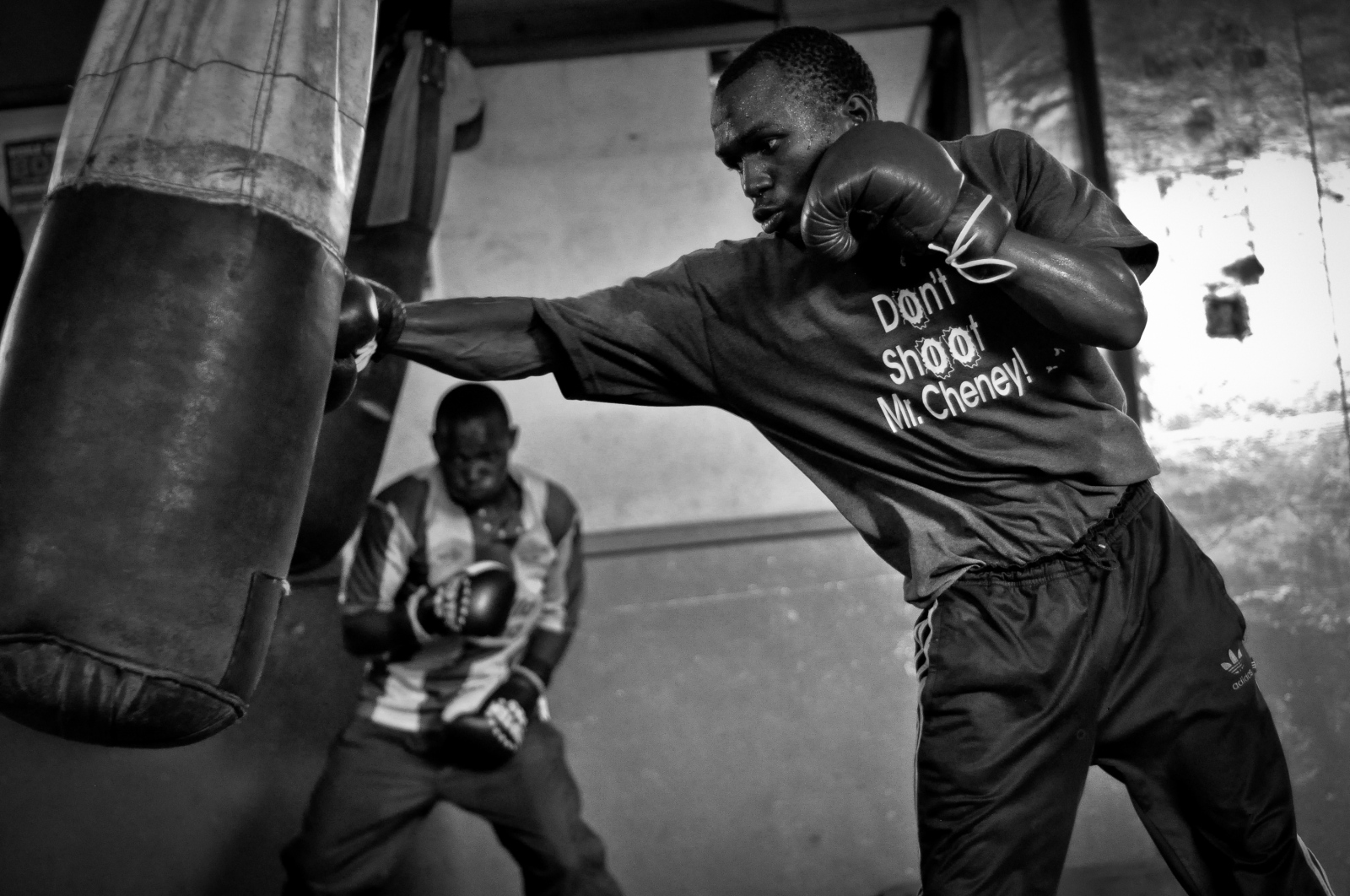 """Photography image - A boxer wearing a """"Don't Shoot Mr. Cheney"""" secondhand t-shirt, bought from one of Nairobi's many second hand clothing markets, practices boxing at a gym in the Nairobi neighborhood of Pamwane, Kenya."""