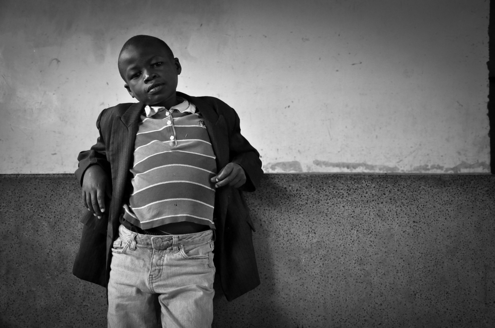 Photography image - A young child stands on the sidelines of a boxing gym in the Nairobi neighborhood of Mathare in Kenya.