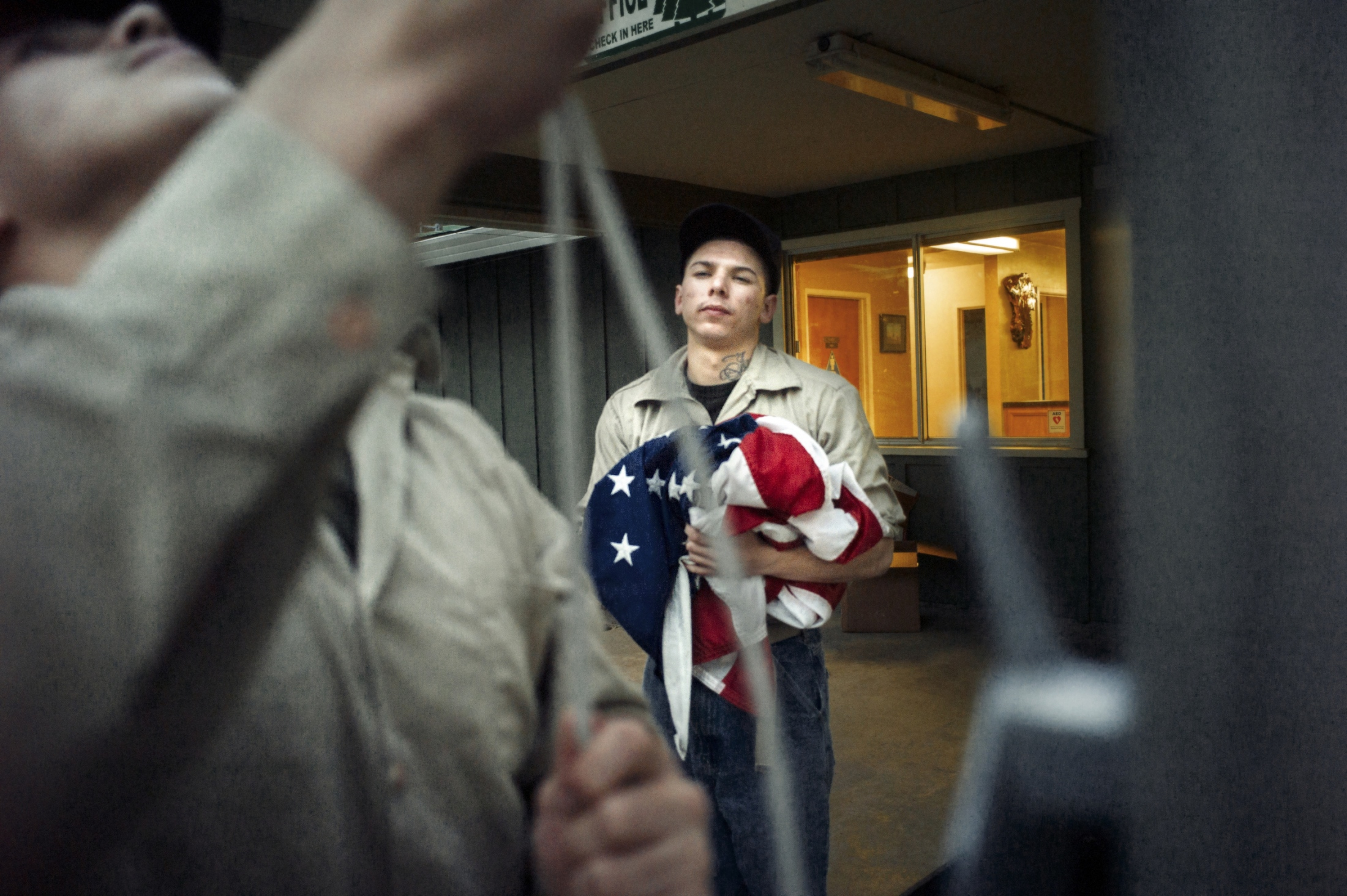 "Inmate Marcus Tapia reluctantly collects the American flag at the end of the day, after being ordered to to so by prison guards.  Tapia was serving time for firearms possesion with added time for a ""gang enhancement,"" but would soon be ""rolled up"" (removed) from the camp for fighting and sent back to a traditional prison institution."