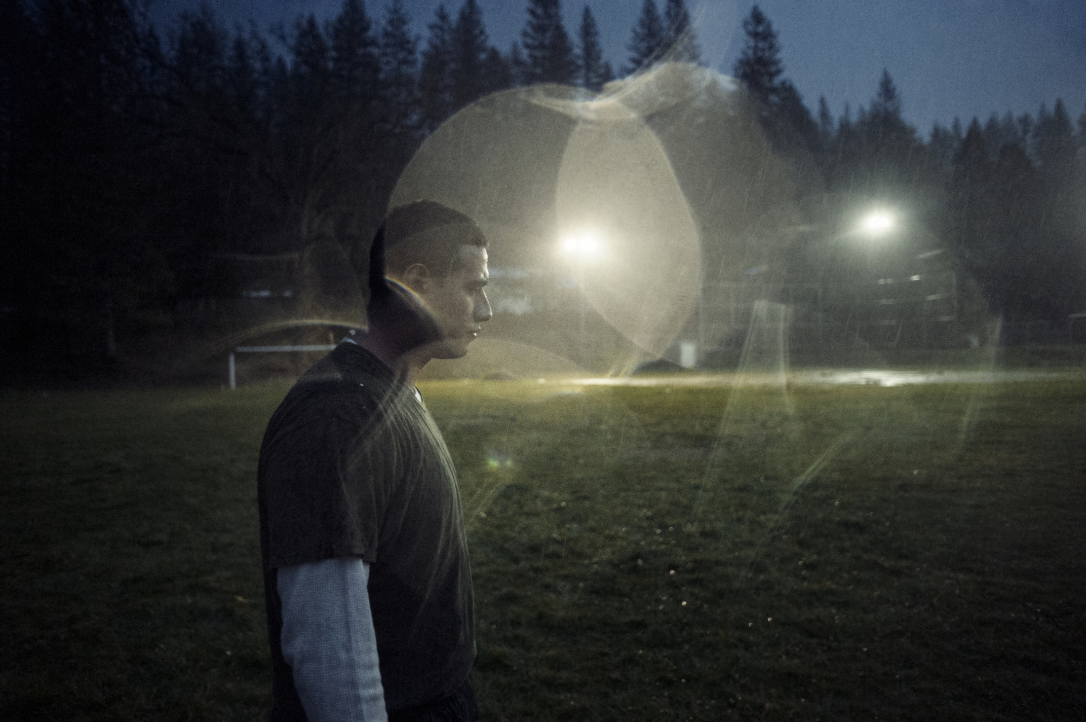 A Pine Grove inmate pauses between plays, while playing football in the pouring rain.  Earned by avoiding fights, the inmates cherished the few times they were allowed to play ball.