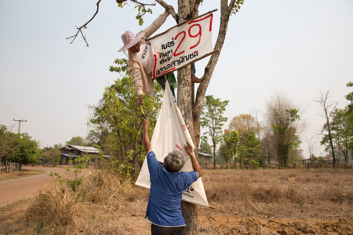 In a remote district Sakhon Nakhon Province in Northeast Thailand, Commoners Party members nail the party's handmade banners to trees. Number 29 is the number of that areas candidate for the party, a man called Sanjiam Sutsaiya.