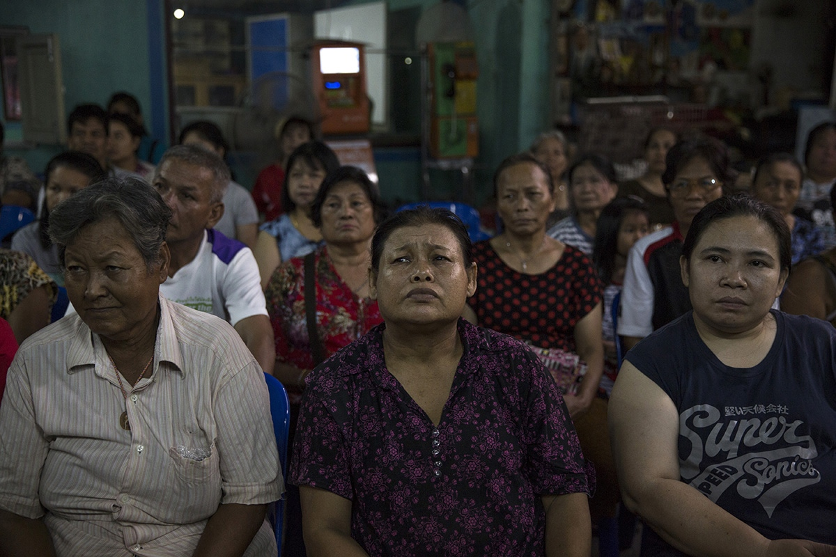 At a slum community on the outskirts of Bangkok locals gather to listen to two members of The Commoners Party who were invited invited to come and put their policies forward to the local people. This community is typical of The Commoner Party members being from the working class and who for 40 years have fought to stay on this piece on land.