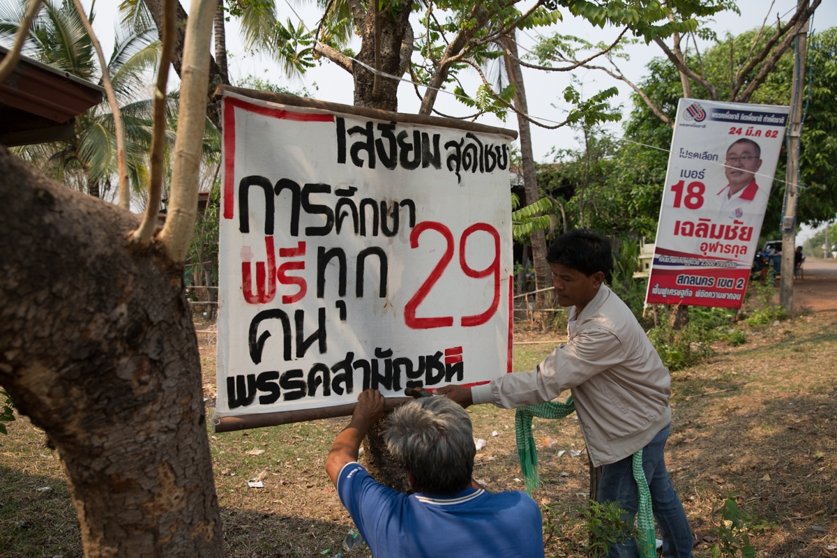 In a remote district Sakhon Nakhon Province in Northeast Thailand, Commoners Party members nail the party's handmade banners to trees. 29 is the number of this areas party candidate and the message offers free health care for everyone.