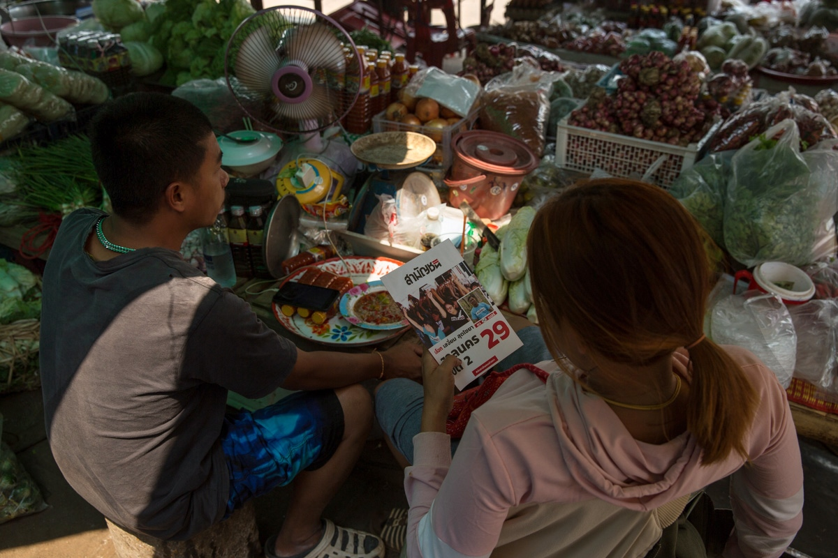 Market vendors in the remote district of Kusuman in Sakhon Nakhon Province read a Commoners Party flyer they have just been given.