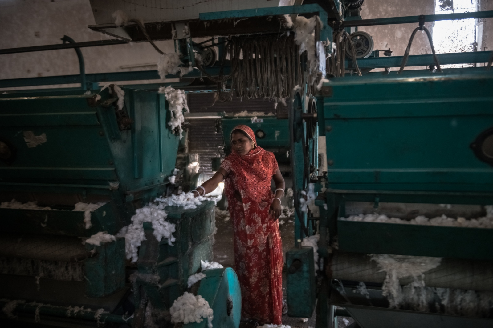 Manjula Popat clears cotton from processing machines at the Radhe Industries cotton-ginning factory