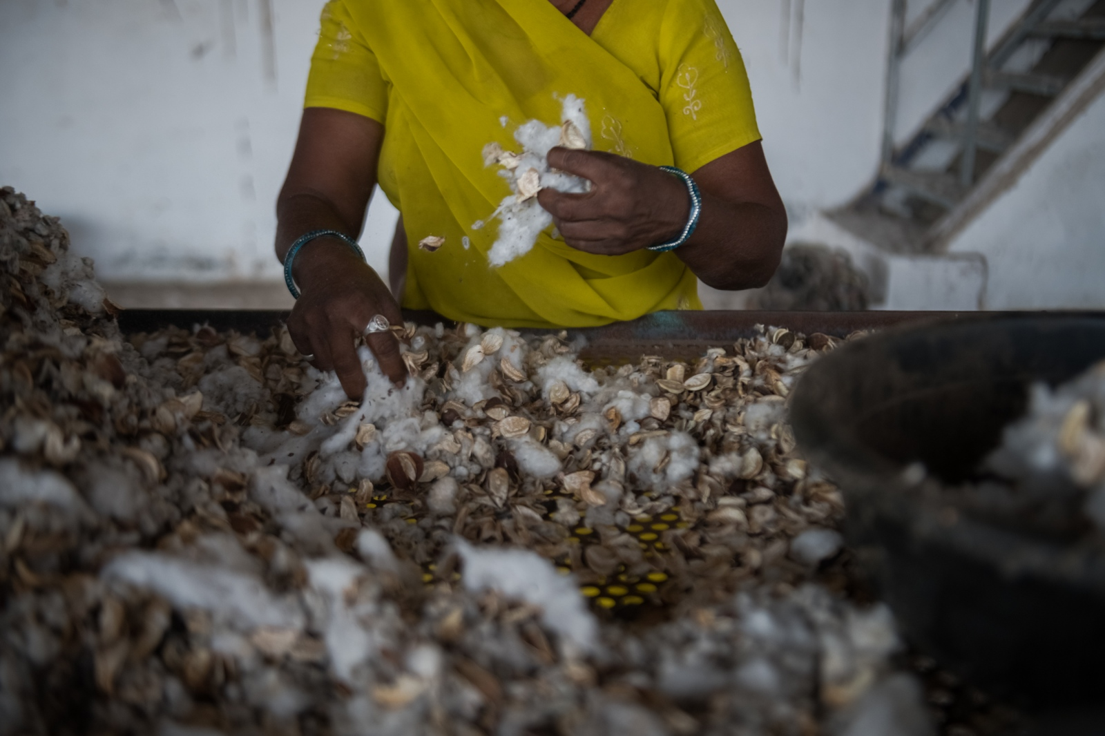 Somu Raju separates raw cotton from husks at the Radhe Industries cotton-ginning factory