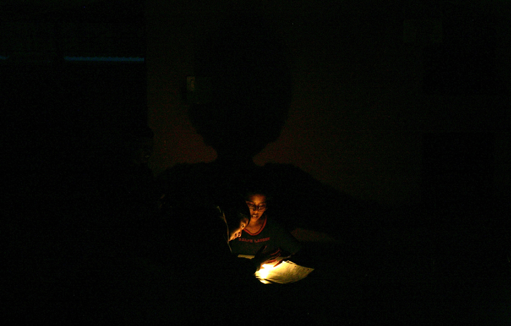Students use candlelight to study their homework. Usually the generators would kick in after an electric outage, but with the current economic climate, the school is cutting back where it can.