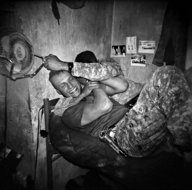 US infantry soldiers (of the 3rd Platoon, Bravo Company, 1st Battalion, 32nd Infantry Regi- ment, 3rd Brigade, 10th Mountain Division), SPC Aldin Zukic, left, and PFC Donald Garab rough house and play fight in their room at COP (Combat Operating Post) Charkh in the south of Logar Province, Afghanistan.