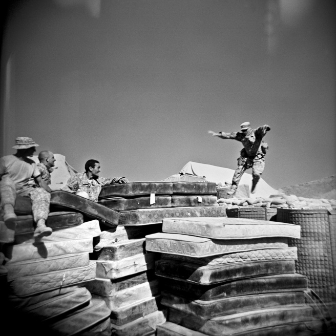 Left to right: US infantry soldiers (of Bravo Company, 1st Battalion, 32nd Infantry Regiment, 3rd Brigade, 10th Mountain Division), SGT John Virg- adamo, SPC Matthew Ledford, and SPC Brian Lucey watch SPC Adam Ramsey, right, jump onto a pile of mattresses at COP (Combat Operating Post) Charkh in the south of Logar Province, Afghanistan, Sept. 2009.