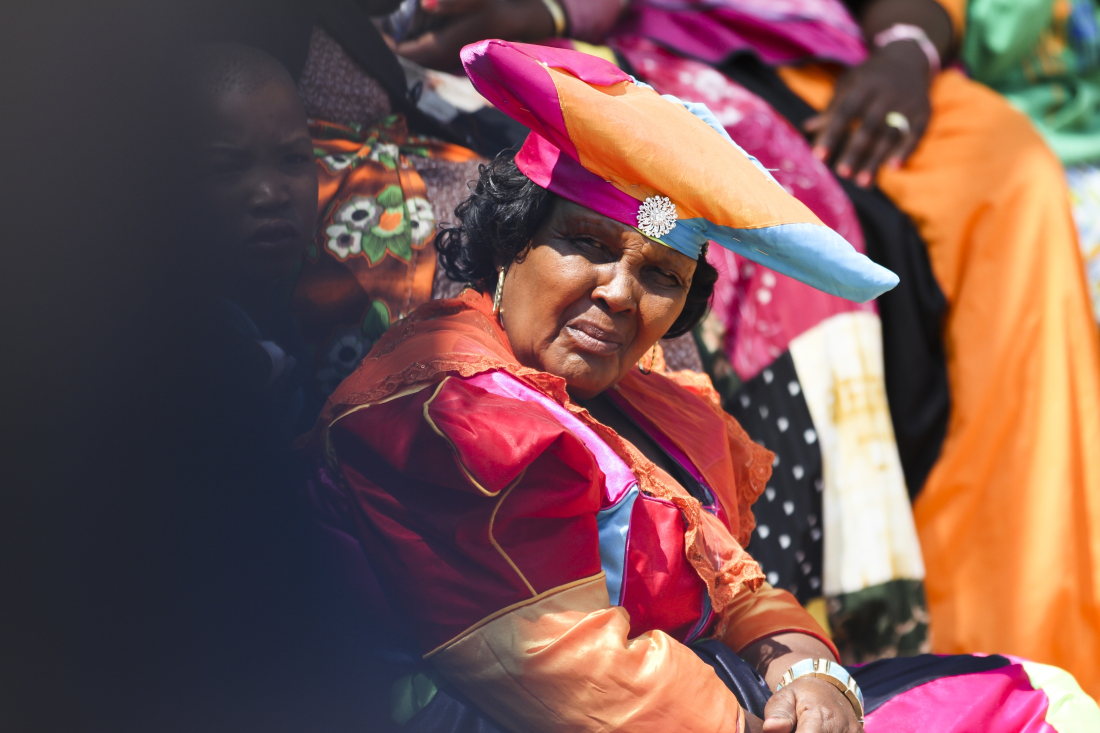 A herero woman wearing her colorful traditional attire. The most distinctive feature of Herero women's dress is their horizontal horned headdress, the otjikaiva, which is a symbol of respect, worn to pay homage to the cows that have historically sustained the Herero.