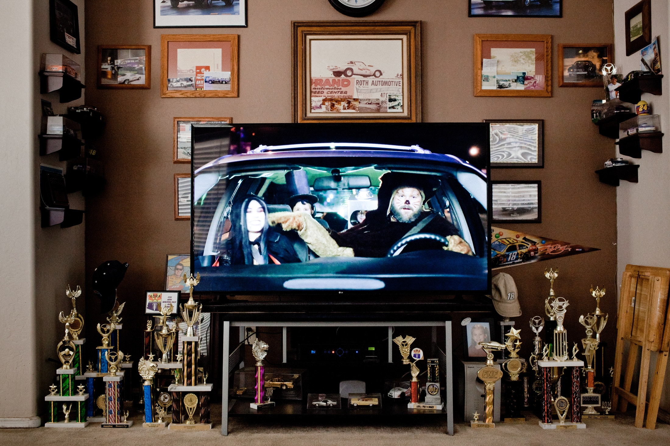 Car racing trophies belonging to Dan Olszewski are standing next the tv set showing a commercial. Olszewski is a hero of vintage car racing, who ofter races at at the Tucson Dragway.
