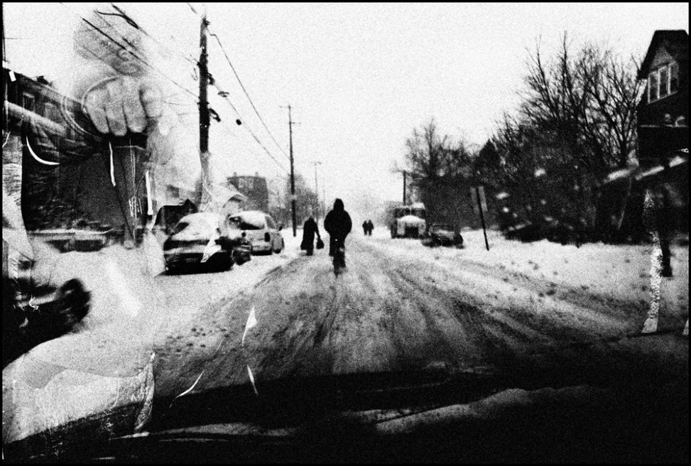 People walk and ride their bike home in the middle of a winter blizzard that dumped almost two feet of snow. A young man poses for a por- trait with his hands out, pre- tending he has a gun, which is a common pose for young people in Chester. (Multiple Exposure in Camera)