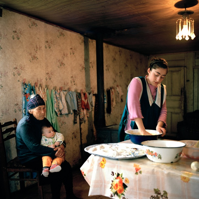 Christina Djologue, 14, bakes a cake while her grandmother Lamara minds baby Gigi. Tagiloni, Gali, abkhazia