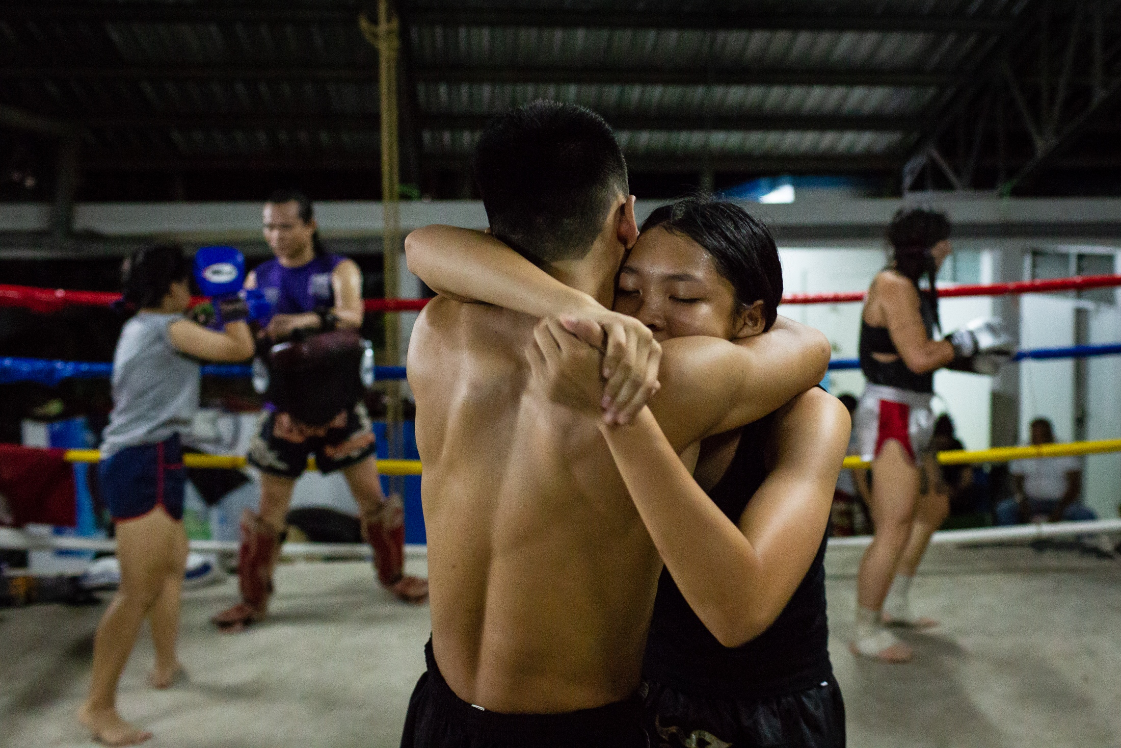 Peem struggles against a fighter during a training session at the Muay Thai Sakchatree gym in Chiang Mai, Thailand, 27th September 2018.  Practising against men is a way for women to measure their strength and to become stronger since men's Muay Thai is usually much more physical.