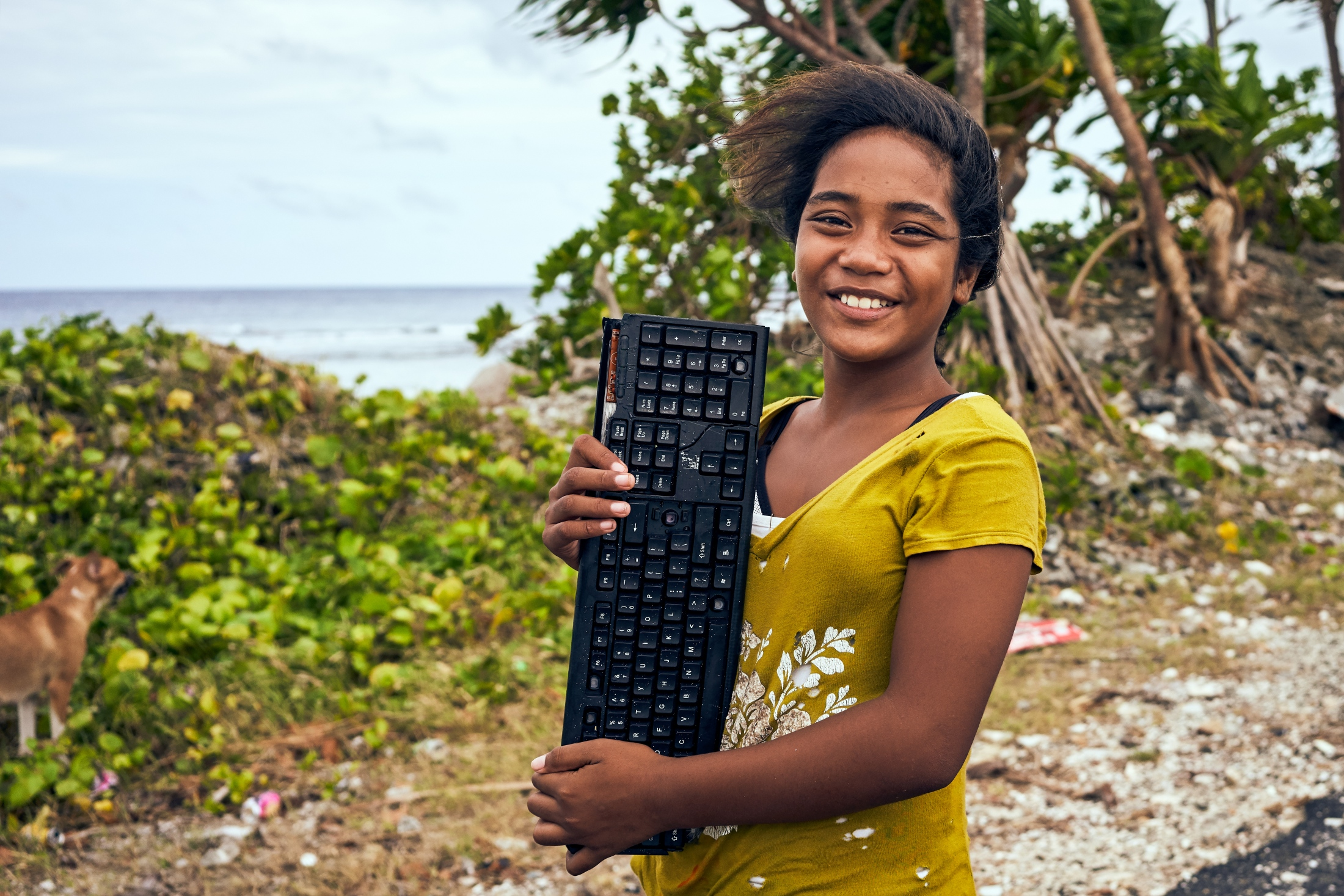 A young Tuvaluan girl poses with a computer keyboard on the narrowest part of the island of Fongafale.  This particular piece of land is approximately 10m wide between the lagoon and the Pacific Ocean, and is often submerged during king tides.