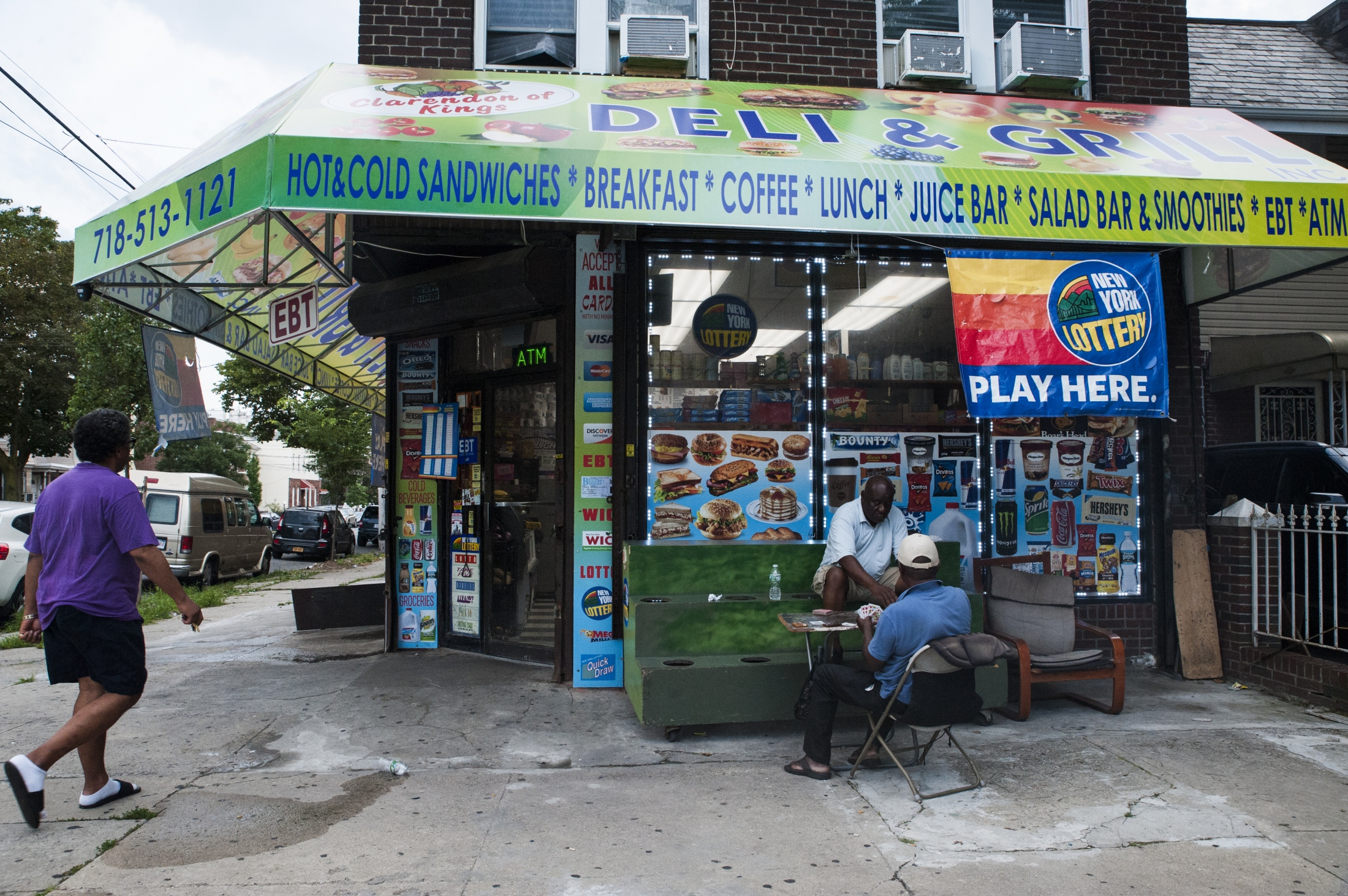 Men playing cards outside a deli on Brooklyn and Clarendon in Flatbush, New York, on July 28, 2018.