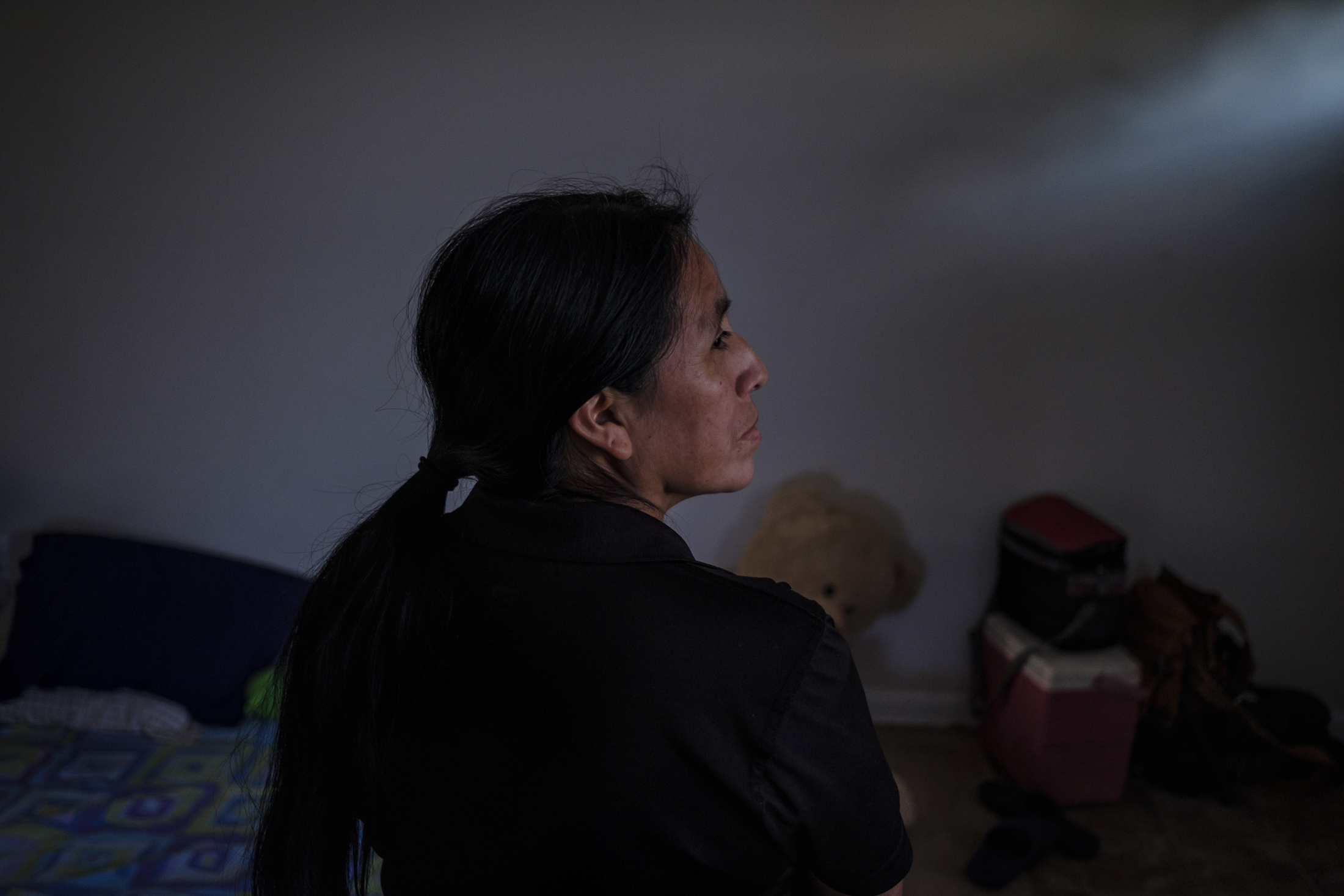 Maria in her home looks out to the window at the sight of an ICE agent, since her day of deportation is current and could arrive at her door any time. María Chavalan Sut, indigenous woman from Guatemala in her home looking out to the window at the sight of an ICE agent, since her day of deportation is current and ICE could arrive at her door any time. She fled to the United States after individuals threatened to kill her in an effort to usurp her land. The seriousness of the threat is not in question: they set fire to her home in Guatemala City while Maria and her family were inside. They lost all their possessions. Maria had to flee Guatemala for her life and was able to come to Virginia. She has been working multiple jobs in order to send money back home to support her children and to rebuild the home her family lost in the fire. Employers in Guatemala would not hire her because she is an indigenous person. Even still, she taught mathematics to underprivileged children and also worked at a self-publishing company producing materials in her native Keqchikel language to help keep it from dying out.