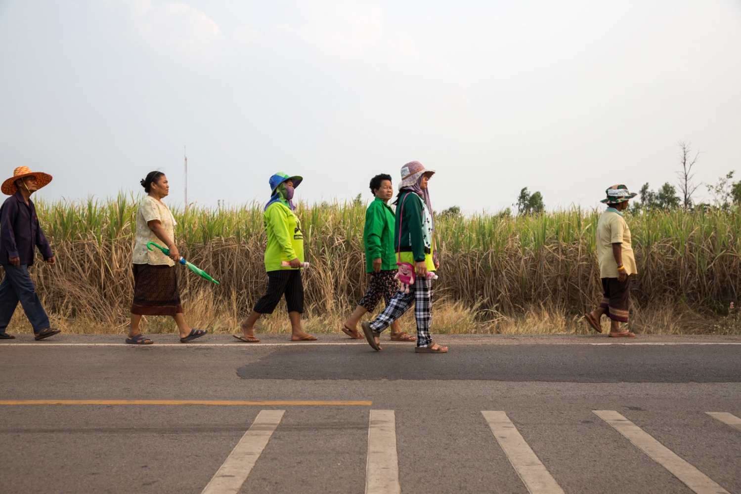 Members of the Wanon Niwat environmental group walk around their village collecting donations for a traditional event in which they will bless the spirt of the nearby lake, praying for its longevity.