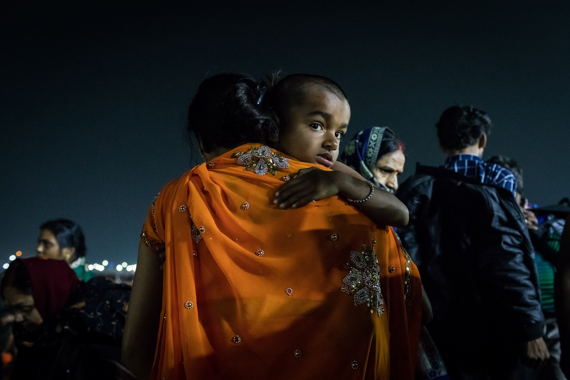A mother carries her child to his first holy bath in a Kumbh Mela, Prayagraj, February 2019.