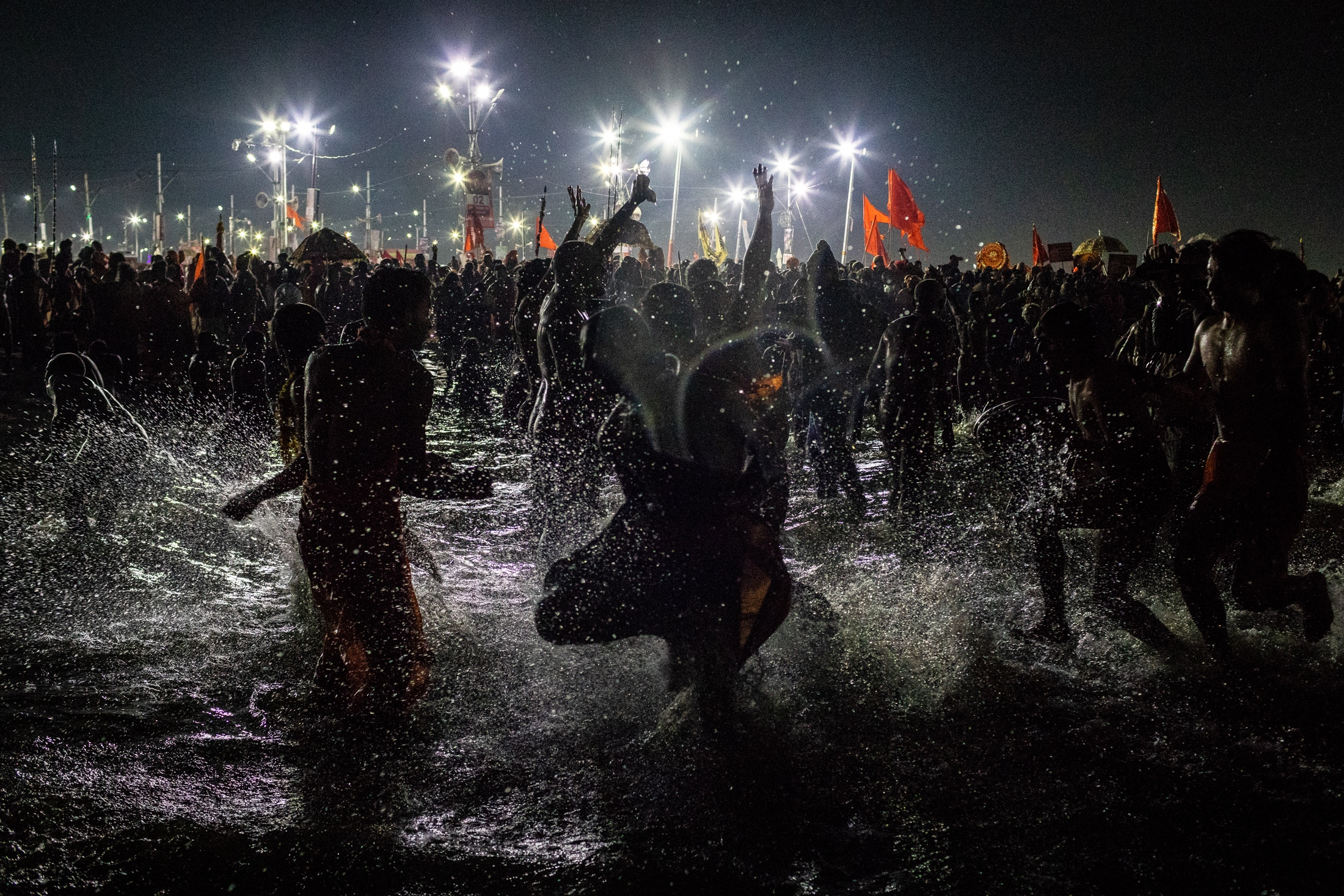 A crowd runs on the Sangam waters during the holy bath during the Kumbh Mela, Prayagraj, February 2019.
