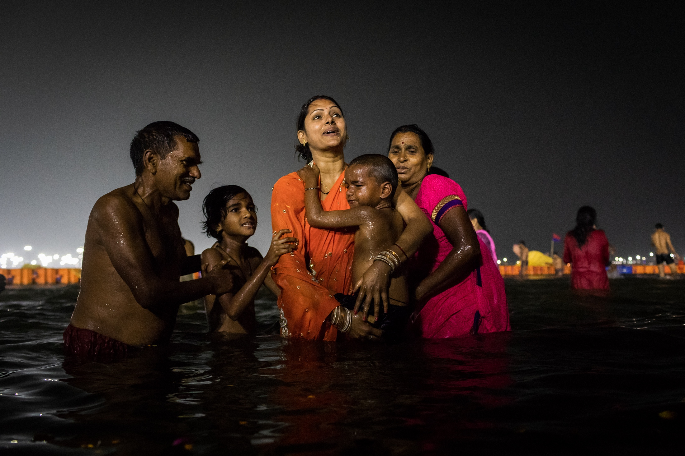 A child surrounded by his family has his first holy bath in a Kumbh Mela, Prayagraj, February 2019.