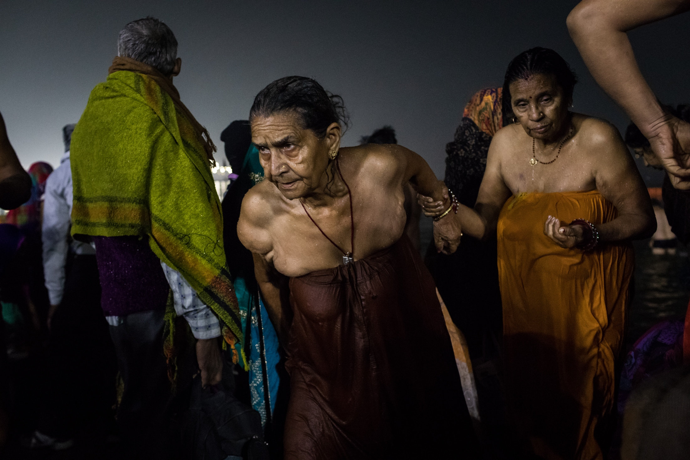 Two pilgrims go through the crowd after their holy bath, Prayagraj, February 2019.