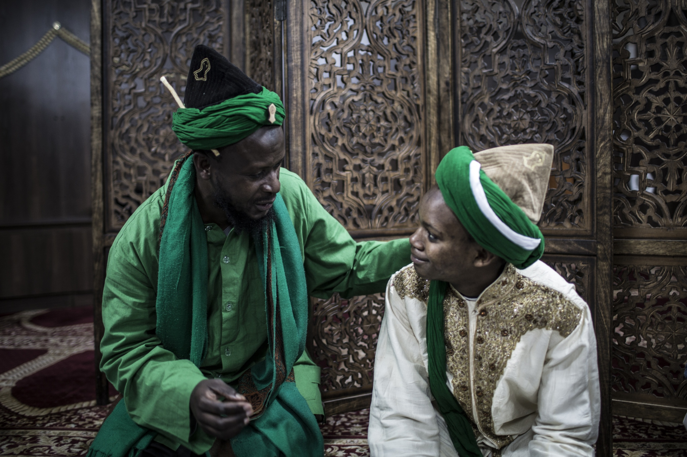 Muhammad Ata (47) (L) and Cassim (17) from Diepkloof, Soweto talk to each other at an iftaar meal at the Naqshabandi Centre.  The centre is rooted in the teachings of Sufism which practices among many things the deep introspection and the embracing of the divine presence of God, the concept of oneness and spiritual connection between all of the living.