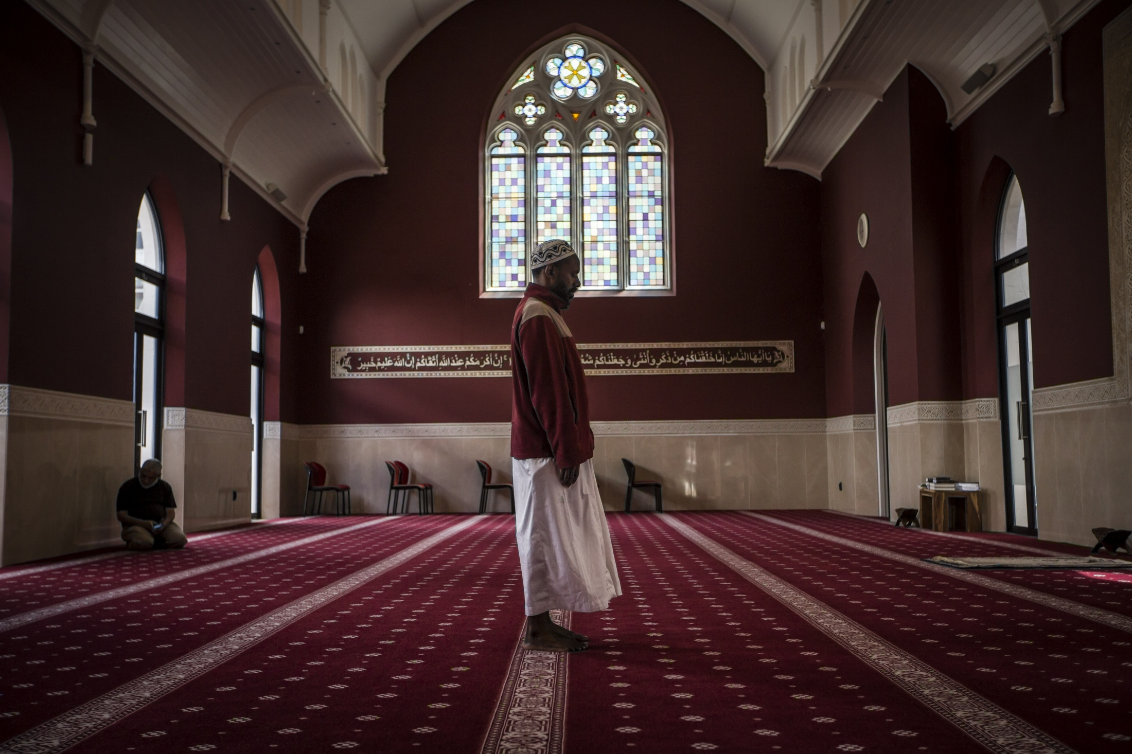 "A man prays in the Heritage Mosque on the Durban Heritage Belt,  Samora Michel Street, Durban South Africa. The 110-year-old building was originally a house of worship for United Congregational Church and while parts of the interior has been restored and most of it revamped in 2017, the Gothic Revival inspired exterior remains unchanged from when it was built in 1904. During the apartheid regime the Group Areas Act limited the number of places of worship that communities of colour could have and so the Grey and West street mosques were the only places for muslims to pray in the entire Durban CBD. In the words of journalist Farook Khan who is pictured sitting in the background: ""The most oppressed people lived in barracks stretching from the waterfront right across what became known as the Central Business District to Sydenham Hill. The minority were white, affluent and in total control of everything, especially their places of worship which excluded their brethren of the darker breed. Some of the privileged class did help build churches for the exclusive use of people of colour, but outside the city limits. But when it came to Muslims and Hindus, no matter their burden or plight, they built their own places of worship. They lived and survived around spiritual places, which became rallying points to celebrate, grieve, protest, resist and unite against oppression."" Surviving two attempted demolishings, today the mosque and adjacent hall has once again become a place of worship and community."