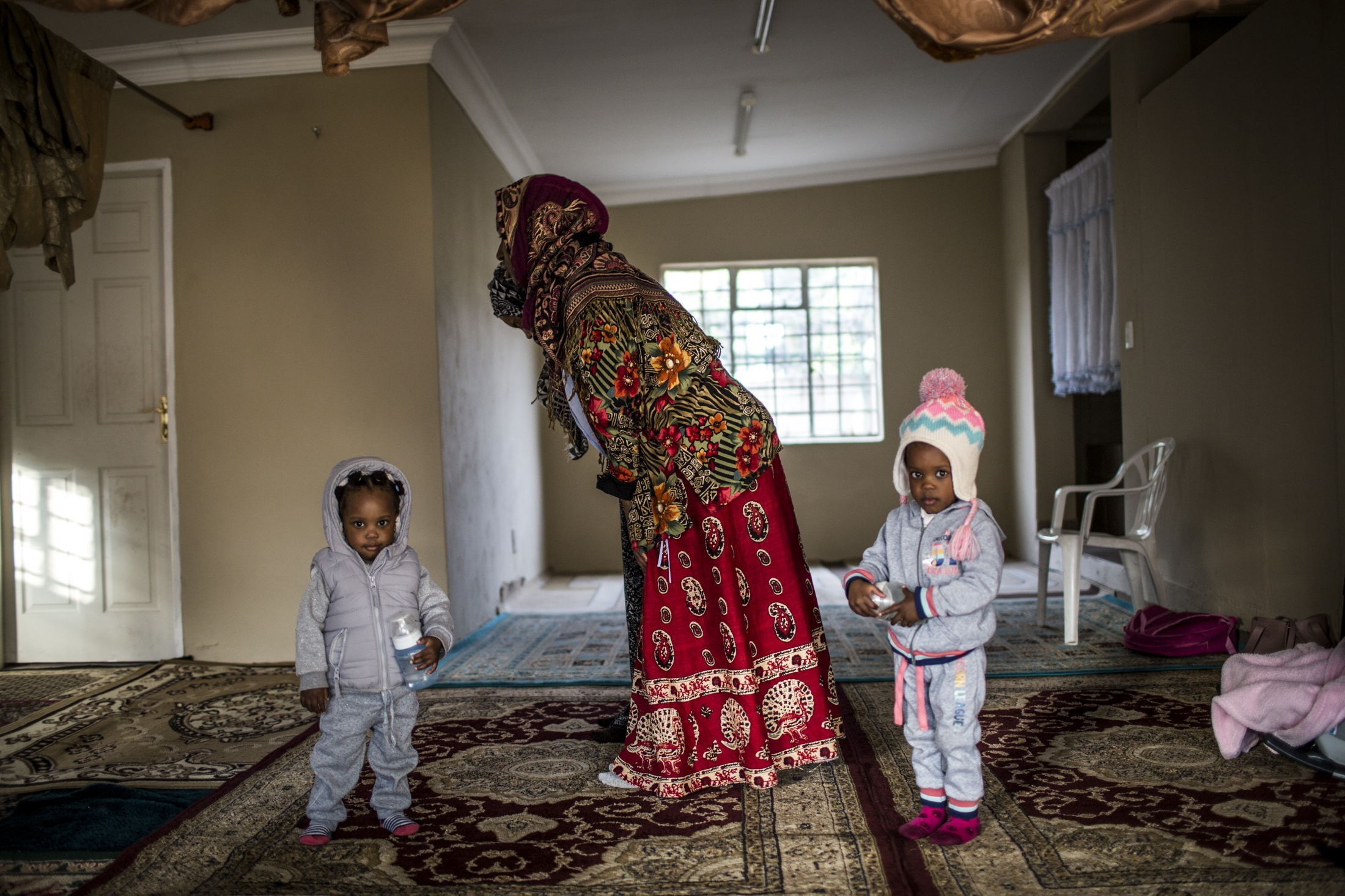 Khalila (R) and Raheema (L) look at the camera while their mother and a friend pray the Asr prayer at the Zawiya Tijani. Pretoria, South Africa. Tariqa Tijani, a line of Sufism traced back to Sheikh Ahmed Tijani in Algeria and Morocco now has followers all over the world. While some Tijani came to South Africa from Mauritanian and Ghana, 95% of the Tijani community in South Africa follow the line of Sheikh Hassan who came south africa in 2002 and united all the communities. The community in Tshwane meet regularly for the daily prayers as well as dhikr.