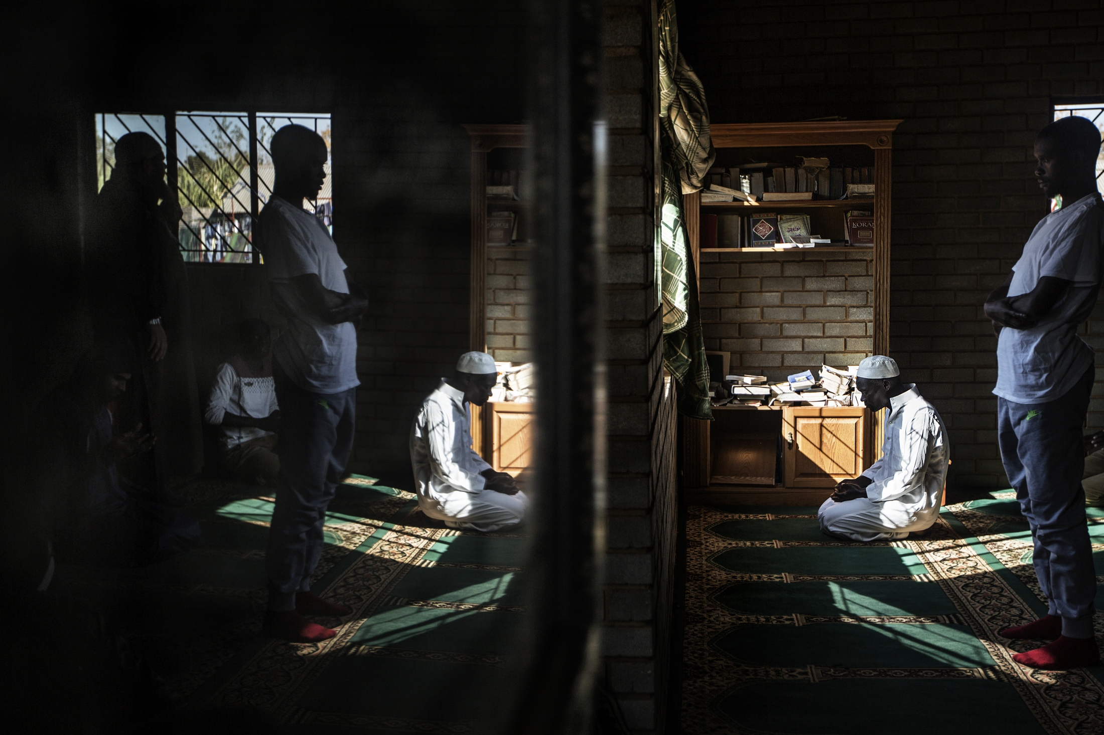 Men perform the second part of the midday prayer out of congregation at the Itirileng mosque in Pretoria during the holy month of fasting, Ramadan.   The masjid, built by a community based non-profit organisation called Neighbourly Needs runs many projects in the community,  including building low cost housing, education programs for children and adults and sustainable development feeding schemes and caters for a large migrant community most of whom are from Malawi.