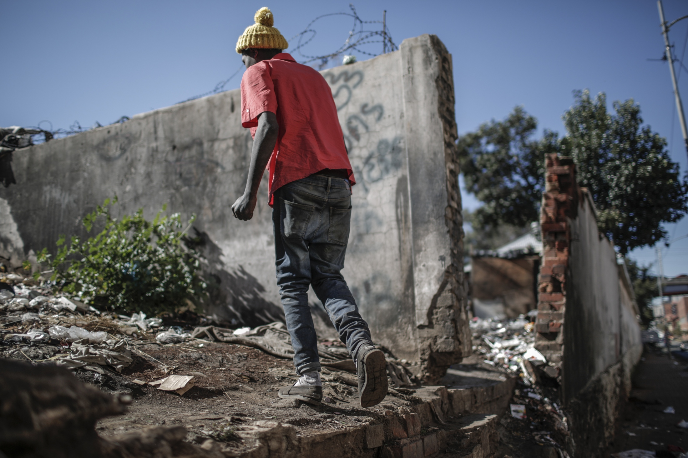 "Neo Pako, 22 , who has been a ""reclaimer"" for three years, walks through the building called Bekezela (Patience) which used to be a school until 2007 and is since the home to many informal waste collectors ""recyclers"" who gather waste from various areas, separate it and transport it on trolleys to recycling plants in the city in Johannesburg."