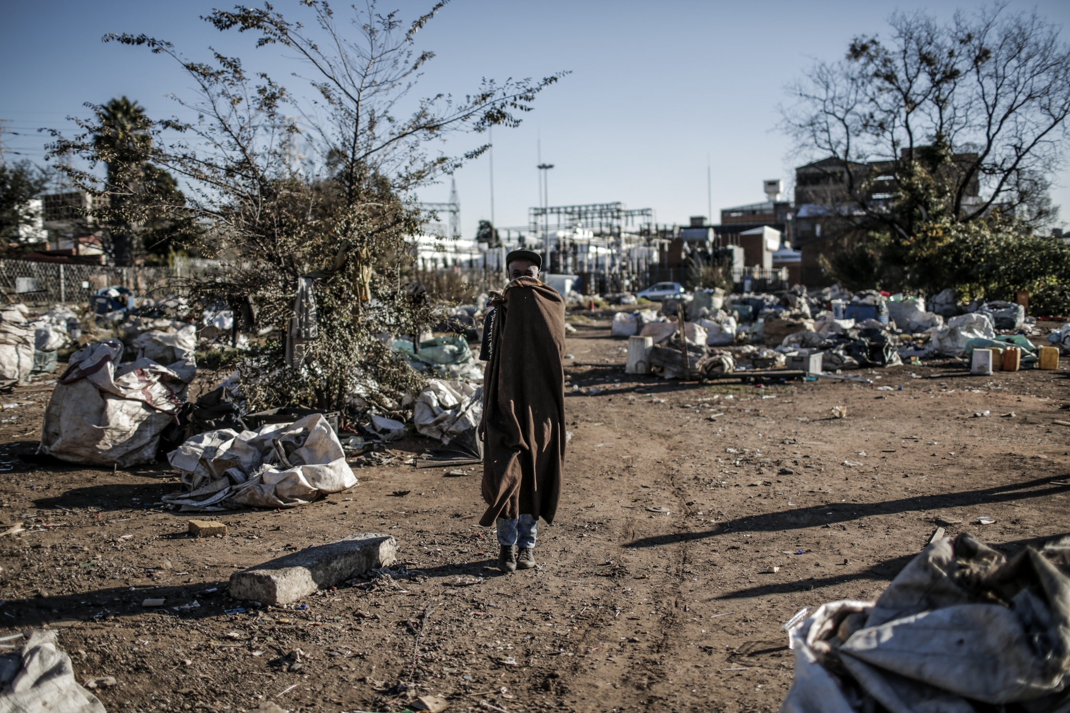 Reclaimer walks through Kwa-Mai Mai recyclers standing area where many reclaimers park their trolleys and separate the waste in Johannesburg.
