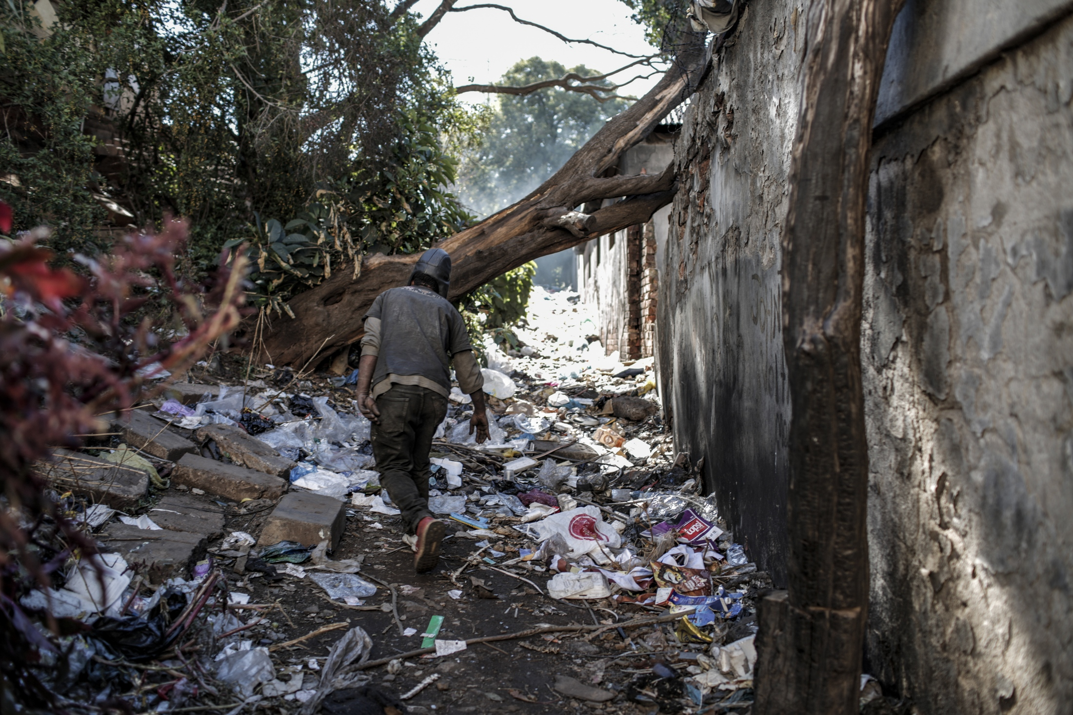 """Plastic lines the sides of building called Bekezela (Patience) which used to be a school until 2007 and is since the home to many informal waste collectors """"reclaimers"""" who gather waste from various areas, separate it and transport it on trolleys to various buy back centres."""