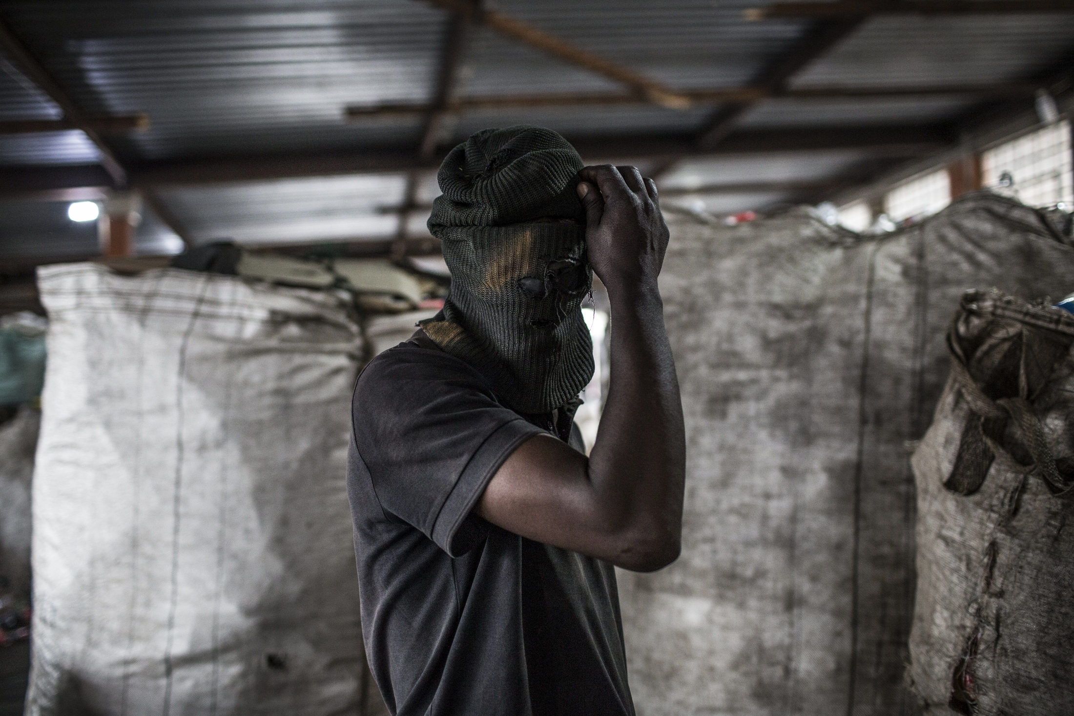 waste picker wears a balaclava at Mudimu Recycling, a buy back centre in Selby, Johannesburg.