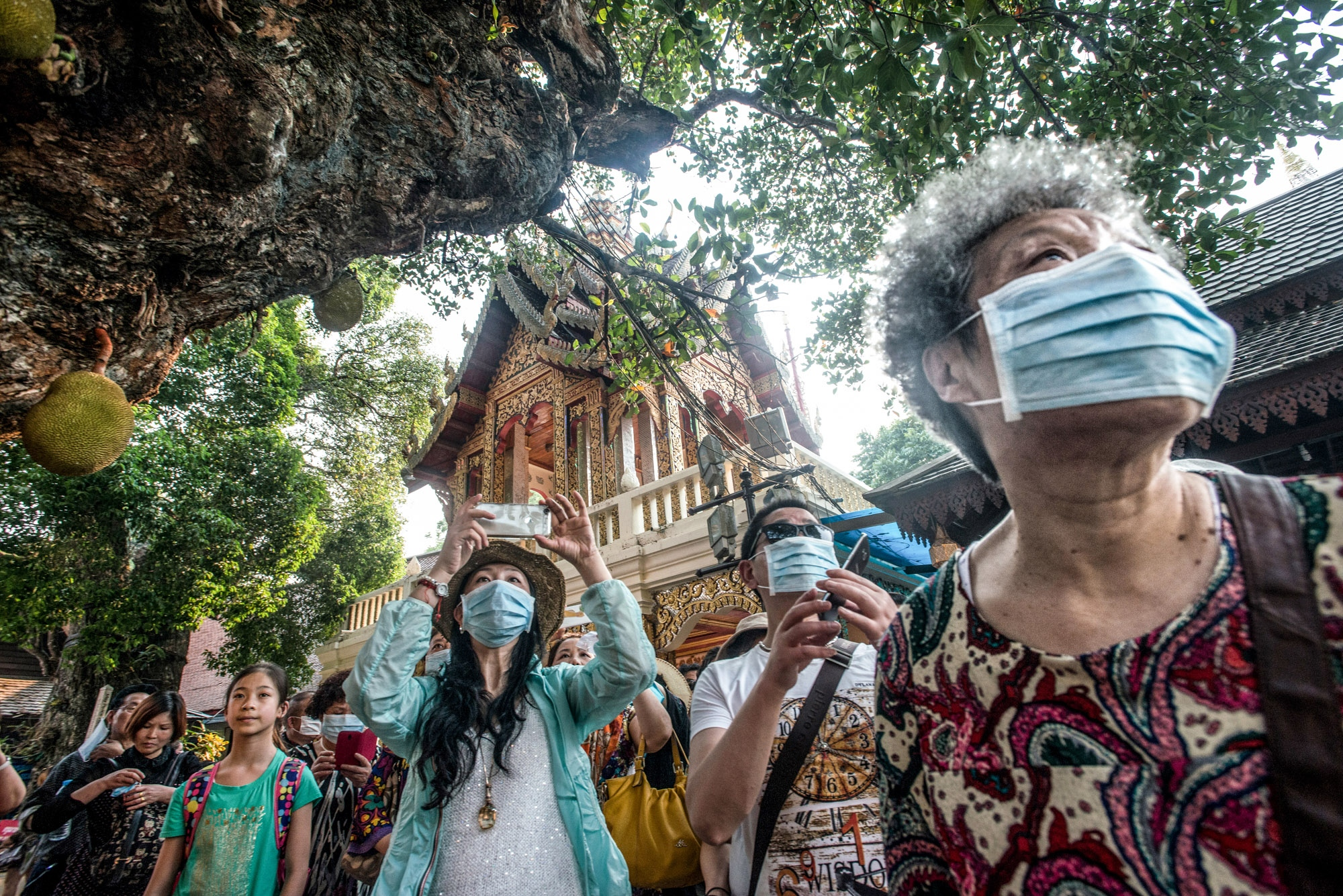 Asian tourists wear dust protection masks during making a visit to tourist destinations in the smog season.