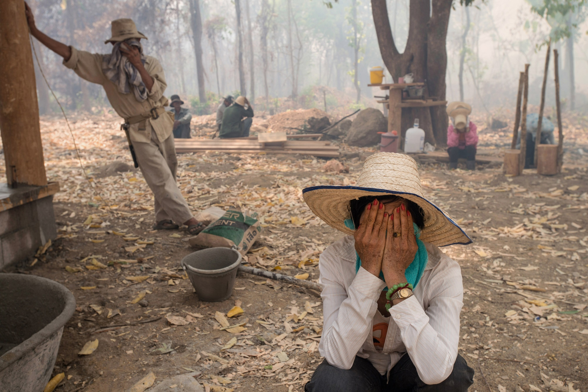 Wildfire occurs during the day time in a place outside of the city. The nearby areas where labors working are covered in haze.