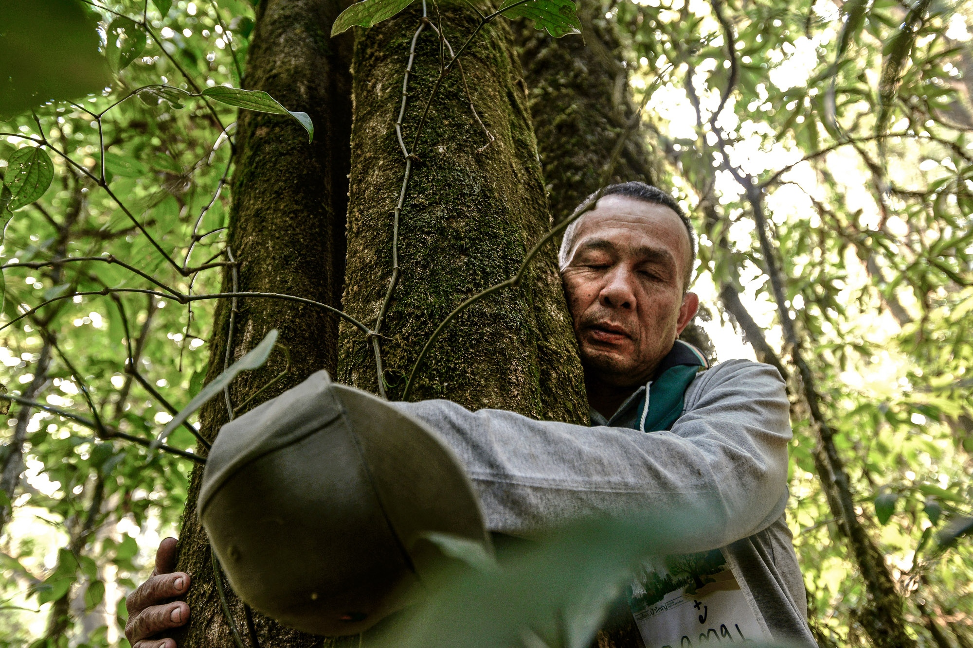 When Ton Maneetor, a senior activist was young, he was shot in his left eye whilst tracking a forest poacher. After losing his eye, he realised the multiple sustainable ways of solving problems and protecting the forest from encroachment should initially come from his understanding, knowledge and experience of the local area despite being partially impaired. During a smoggy season. Ton's children are taught to have a perception of being in harmony with nature and the ideology has been passed down through many generations ensuring consistency throughout. Doi Inthanon, Chiang Mai, Thailand.