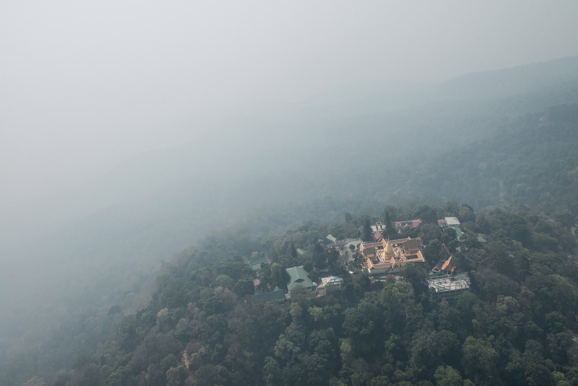 Chiangmai, the city surrounded by mountains is covered in a thick layer of smog during annual wildfire occurrence. Wat Prathat Doi Suthep in Chiangmai, an iconic temple high up in the mountain is also covered in haze.