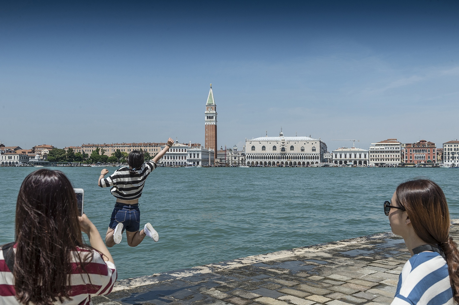 Happy japanese tourists are enjoing Venice from La Giudecca
