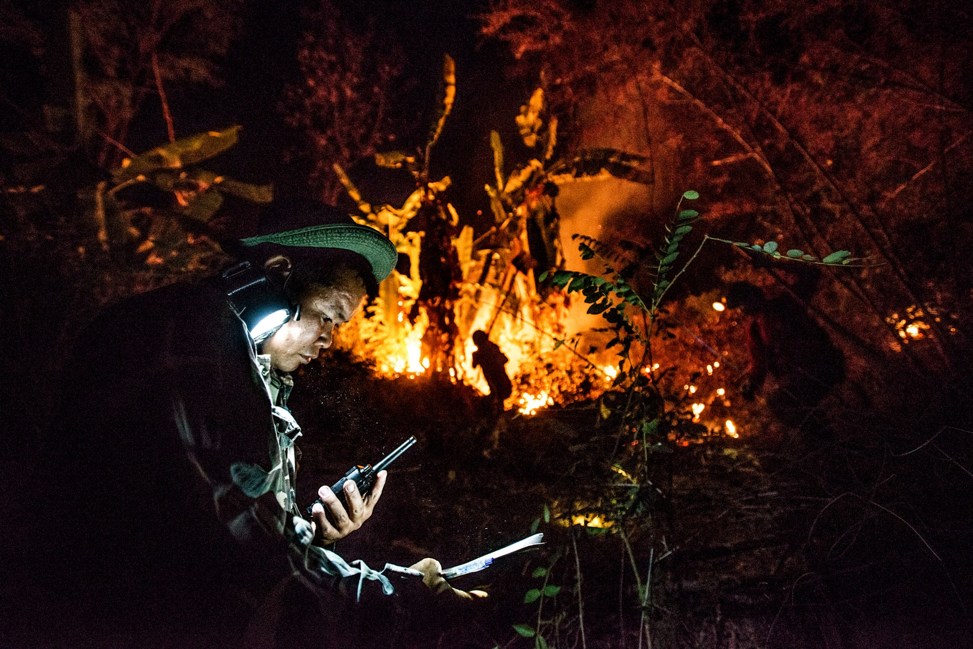 Fire fighters at work battling to put out the forest fires at night which had been reported by villagers. Mae On, Chiang Mai, Thailand.
