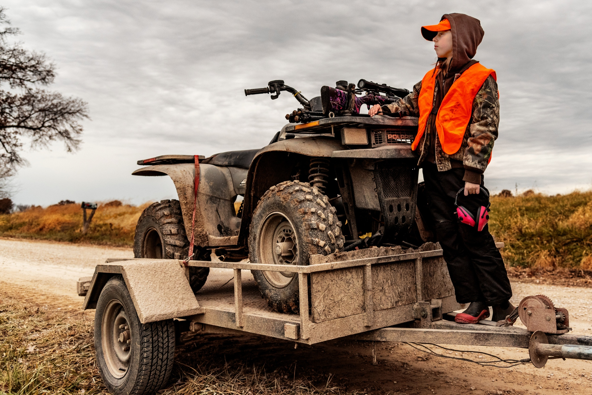 Callie Jennings, 11, waits with her gun resting on the hood of the family four-wheeler for her dad, Michael Jennings, to go check trail cameras on November 23, 2018 outside Centralia, Mo.