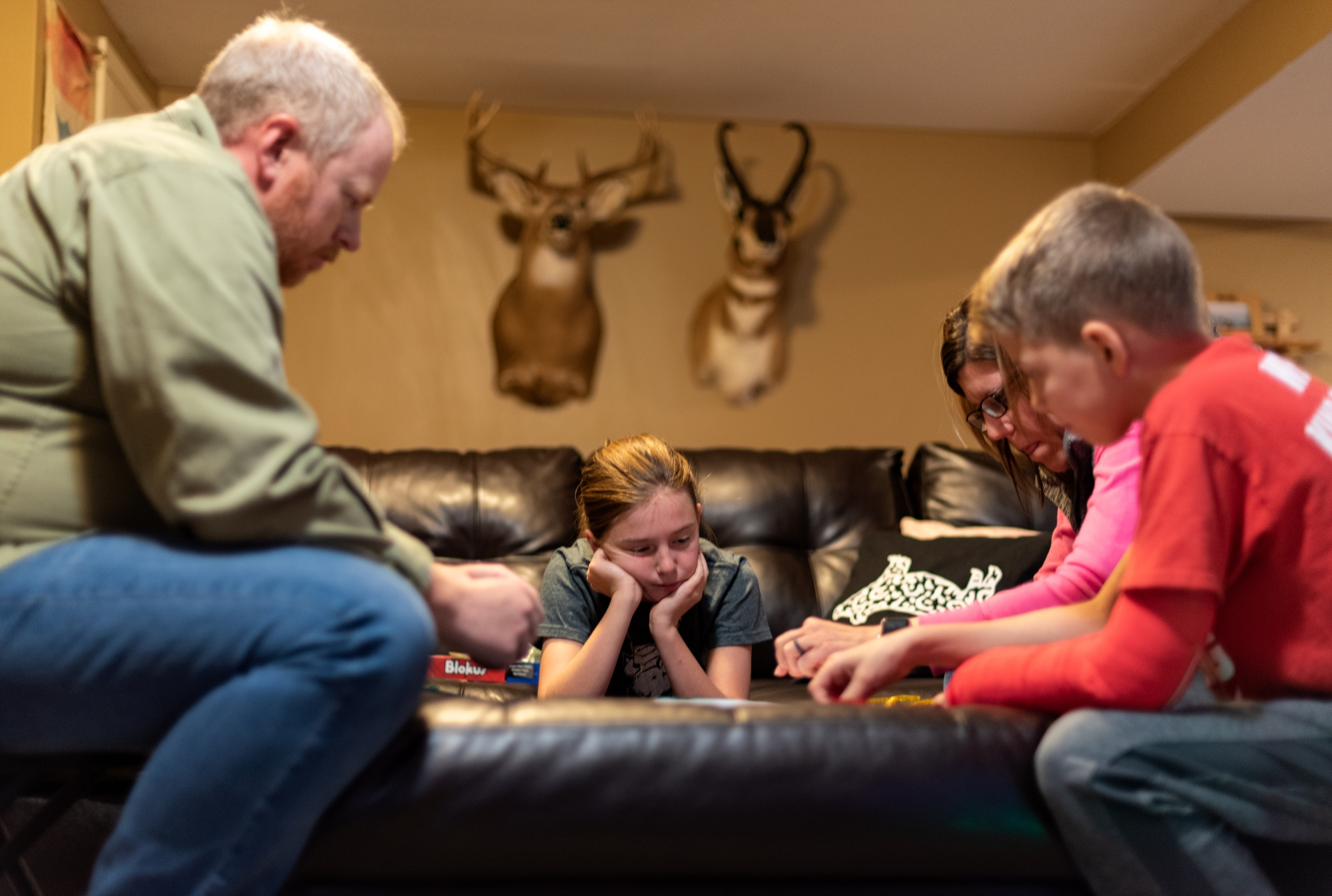"""Callie Jennings, center, plays a board game with her dad, Michael Jennings, mom, Pam Jennings, and brother, Clayton Jennings, on November 26, 2018 north of Columbia, Mo. """"Callie is a board game fanatic,"""" Pam Jennings said. """"Yeah but I'm really bad at them,"""" Callie responded."""
