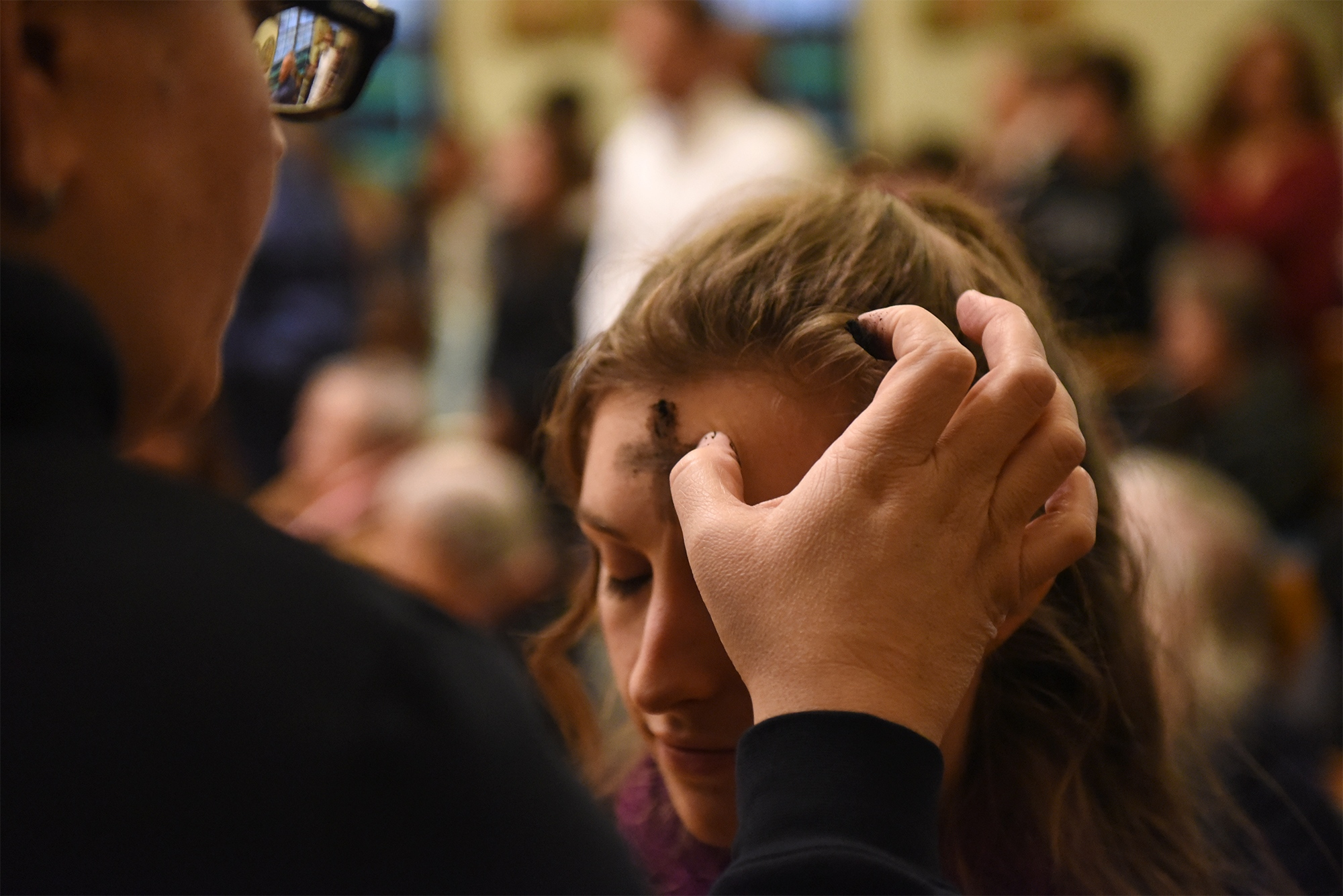 Emily Million receives a cross of ash during evening mass on Wednesday March 6, 2019 at Sacred Heart Catholic Church in Columbia. Traditionally, members of the Catholic Church receive crosses made of ash on their forehead, symbolizing repentance.